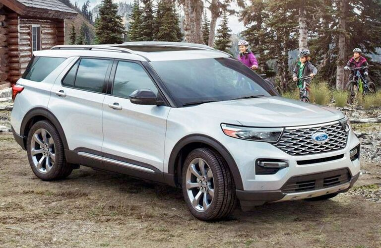 2020 Ford Explorer exterior front fascia and passenger side in front of cabin with family on bike