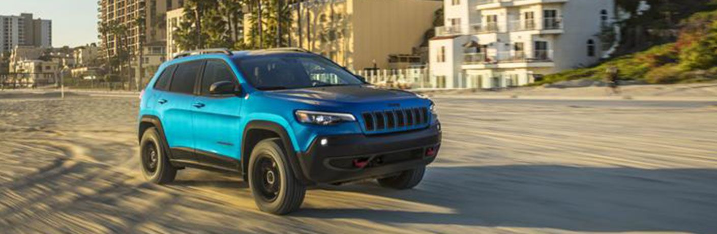 2020 Jeep Cherokee blue driving through sand on beach