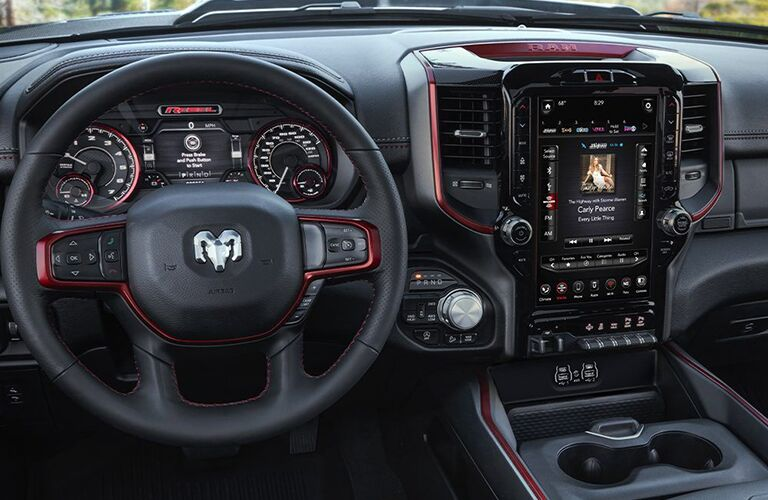 2020 Ram 1500 interior shot of dashboard and console with steering wheel showing large vertical screen