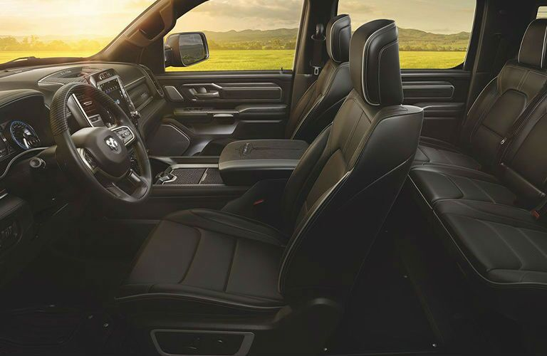 2020 Ram 1500 interior shot from driver side window showing steering wheel both seats center console and grass outside windows