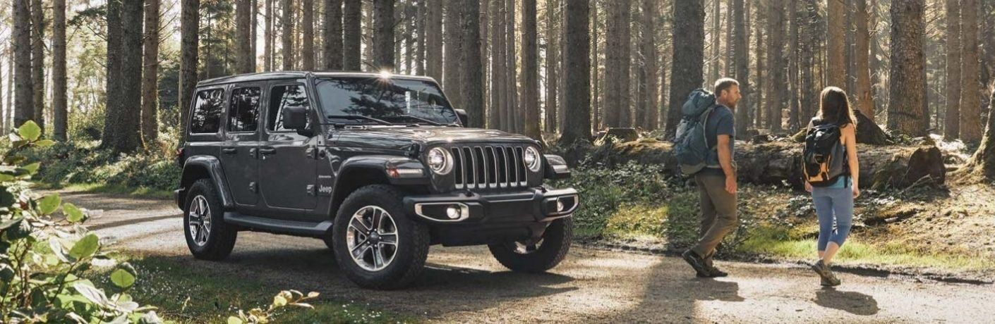 2020 Jeep Wrangler Unlimited parked in woods with two campers