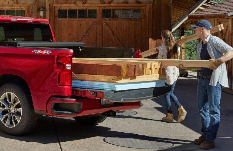 Man and woman loading wood into 2021 Chevrolet Silverado
