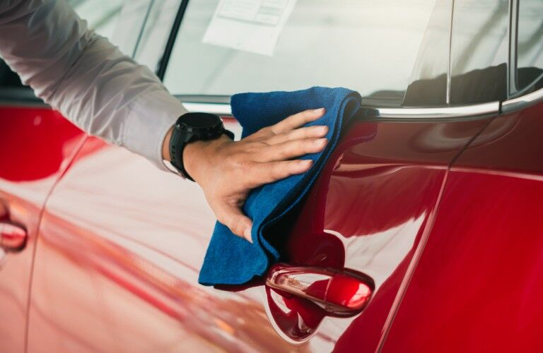 Dealership employee wiping down a car with a cloth
