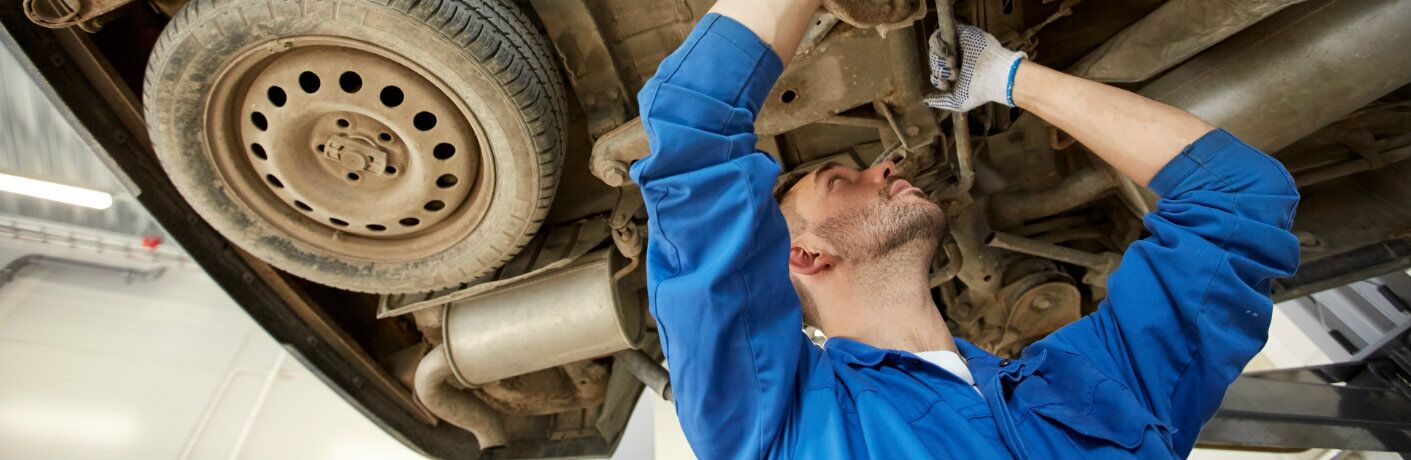 Mechanic working on the undercarriage of a vehicle