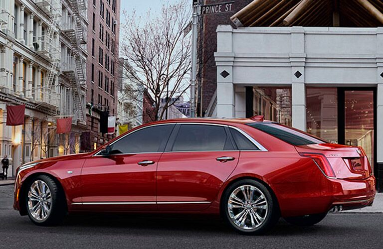 2017 Red Cadillac sedan driving downtown