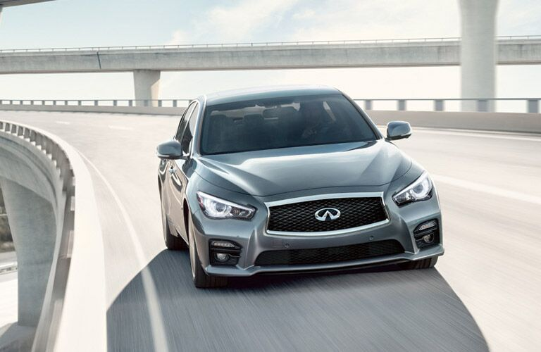 Front view of silver INFINITI Q50 driving on highway entrance ramp