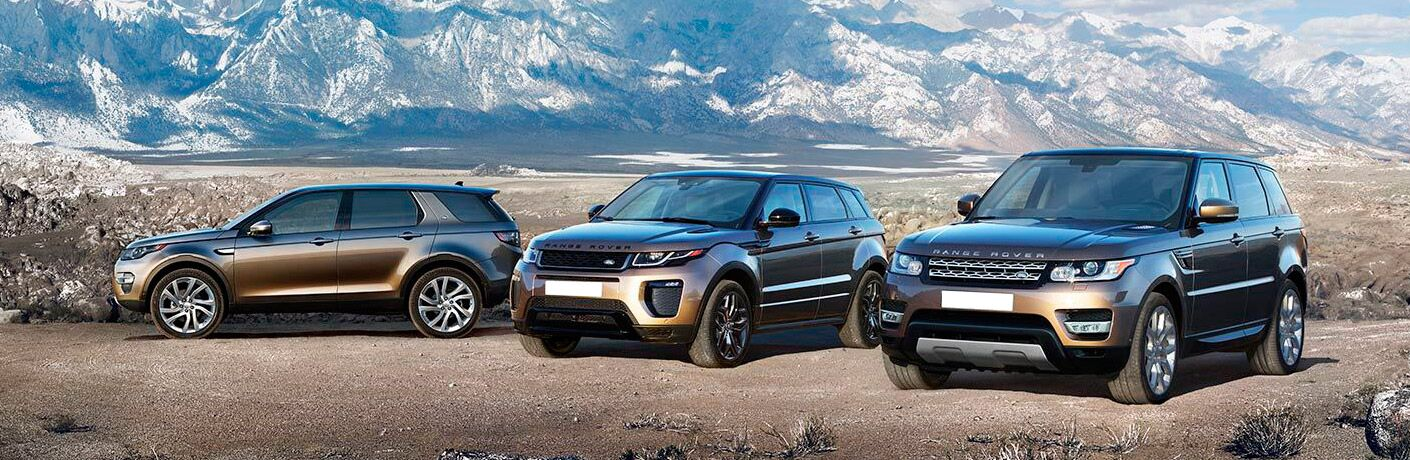 Three Land Rover models sitting on a paved area in front of mountains