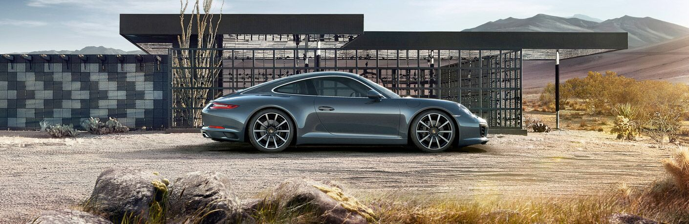 2019 Porsche 911 parked in front of a modern building in the desert