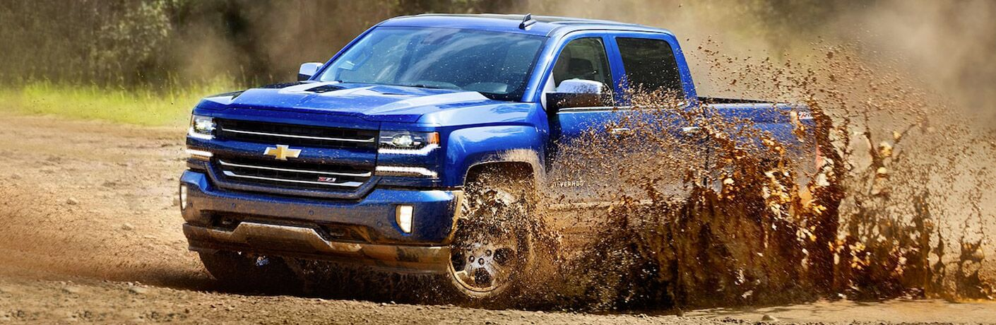 2018 Chevy Silverado driving through a mud puddle
