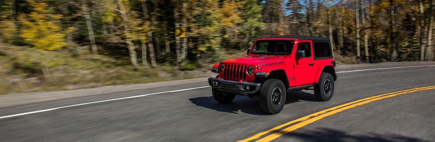 2018 Jeep Wrangler in red driving down a road in the woods