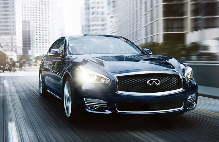 Front view of blue INFINITI Q70L with front headlights illuminated