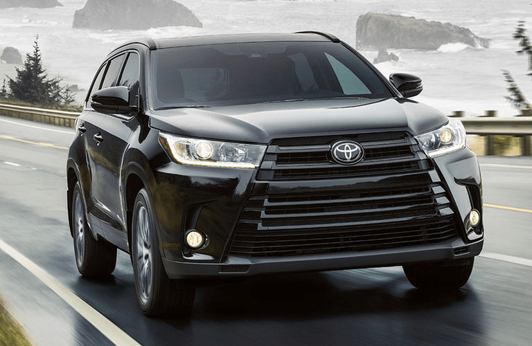 2018 Toyota Highlander driving on a bridge past the ocean