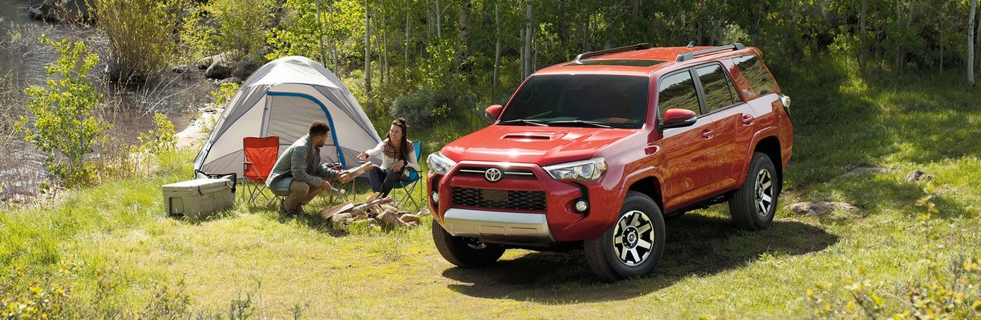 A man and a woman camping next to the 2020 Toyota 4Runner
