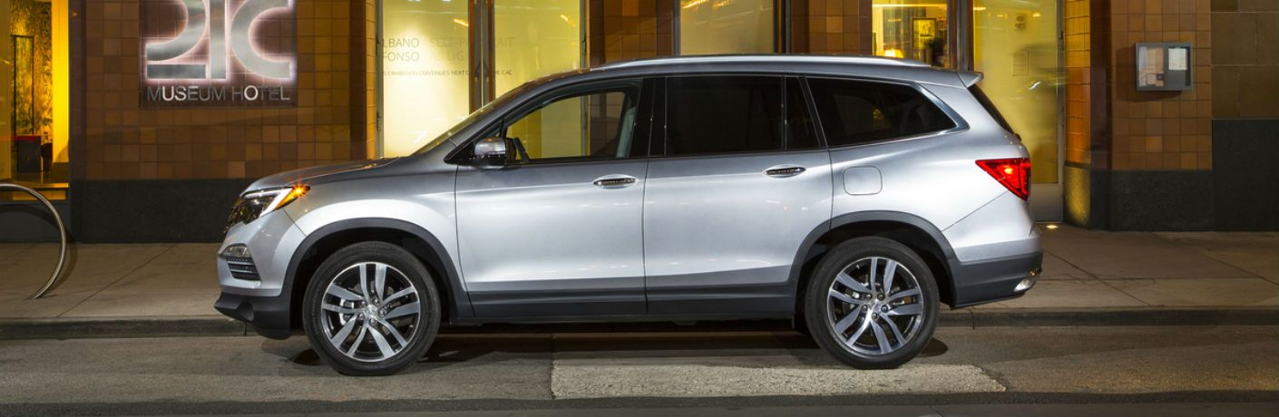 Driver side exterior view of a gray 2018 Honda Pilot Elite