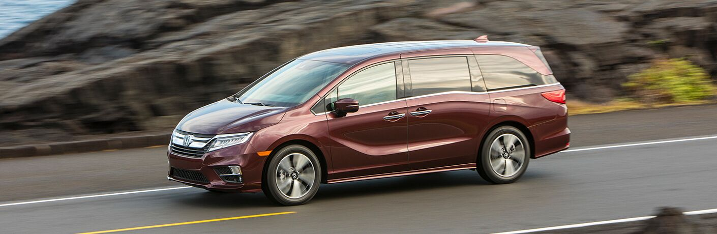 Driver side exterior view of a red 2019 Honda Odyssey