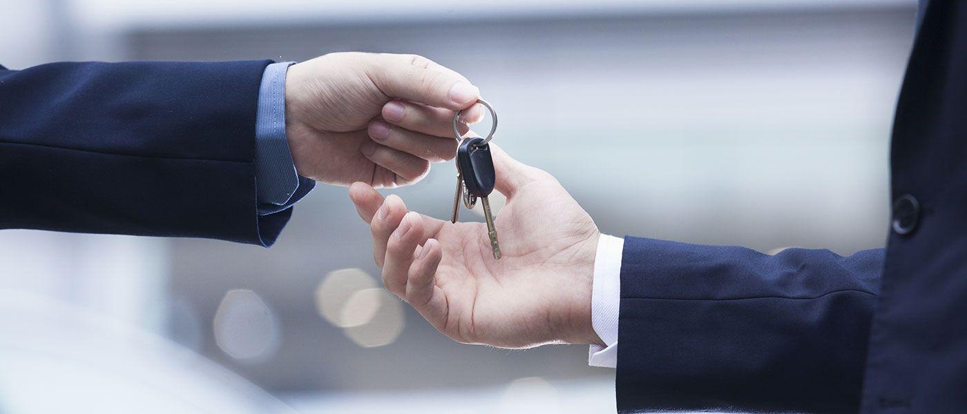 Man handing car keys over to a family