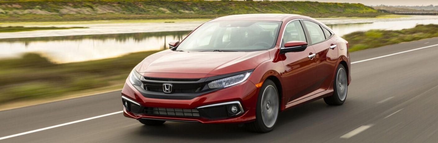 Red 2020 Honda Civic Sedan Touring driving on road in front of water and palm trees from exterior view