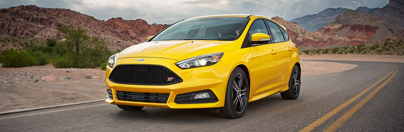yellow ford focus driving on road by mountain