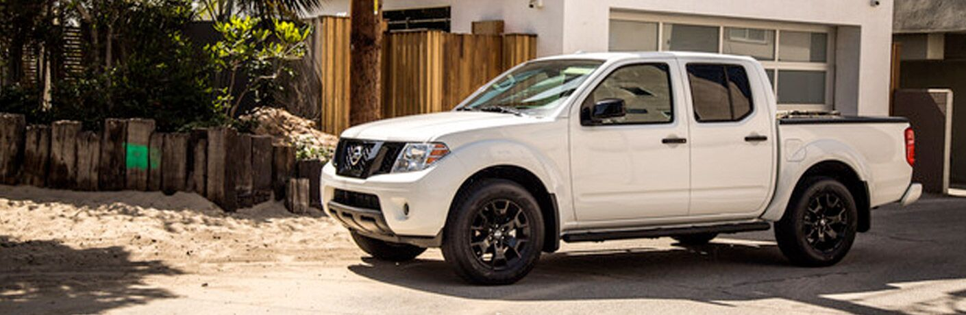 side view of white 2019 Nissan Frontier parked by a house