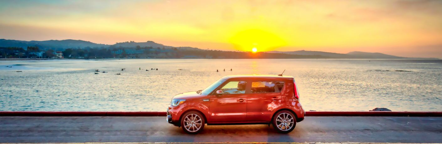 2019 Kia Soul driving by water with a sunset