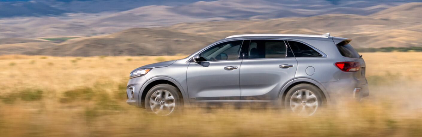 left side view of silver kia sorento driving by tall grass