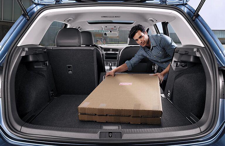Man loading cargo area of 2019 Volkswagen Golf