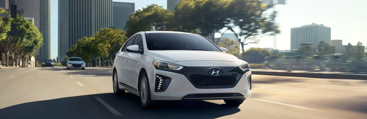 white 2019 Hyundai IONIQ Electric Plus by a city