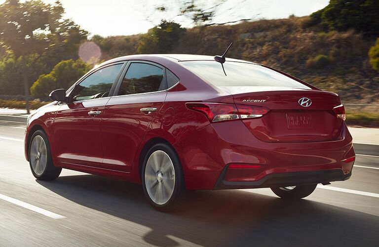 red 2019 Hyundai Accent driving on road back side view