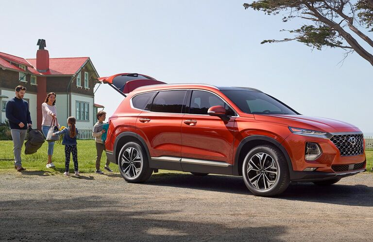 orange hyundai santa fe with family