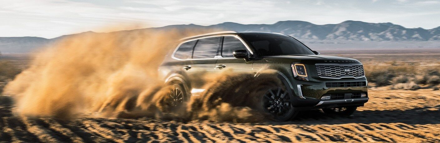 2020 Kia Telluride green side view sliding in the sand