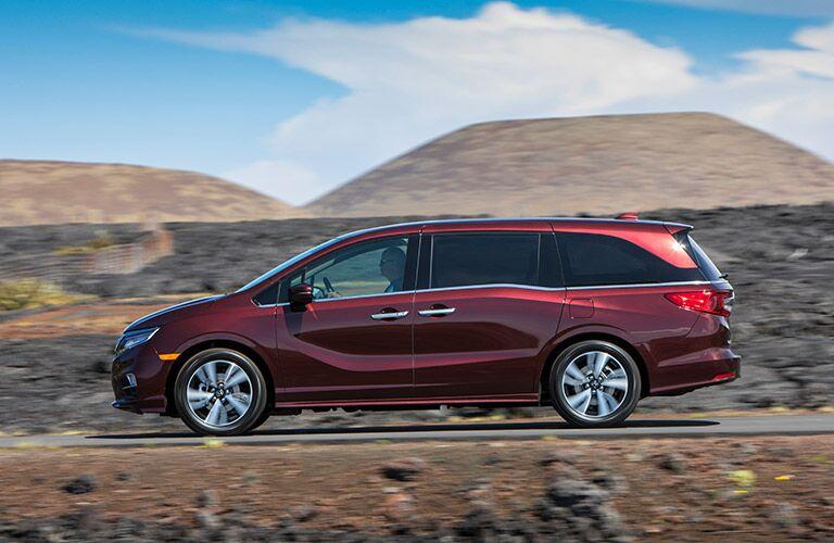 Maroon 2019 Honda Odyssey Side Exterior on a Desert Road