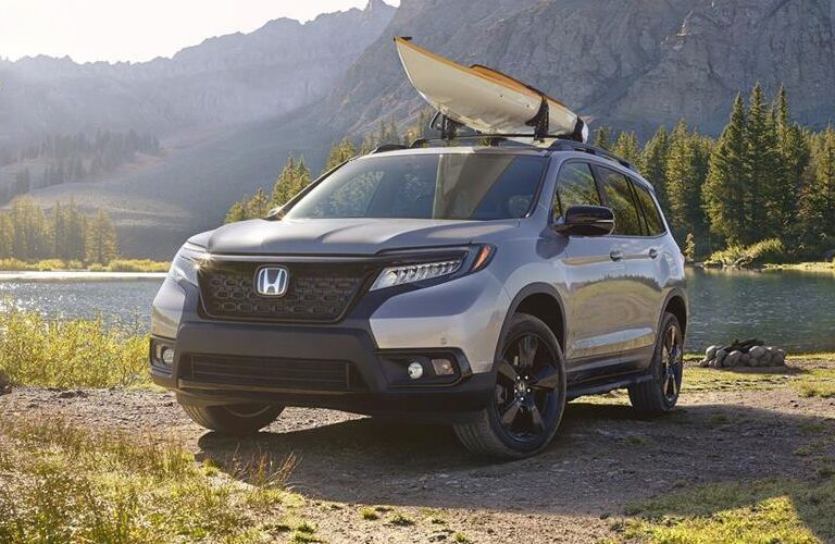 Silver 2019 Honda Passport Next to a River with a Kayak on the Roof