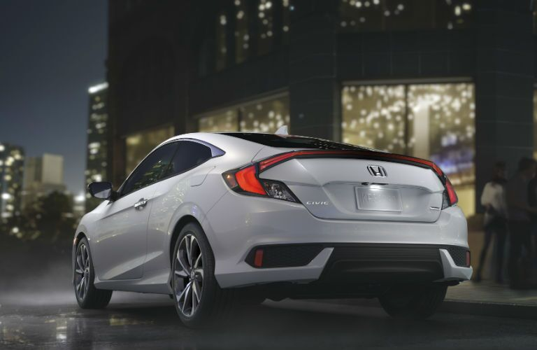 2019 Honda Civic Coupe rear profile view as it is driving at night
