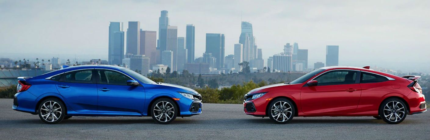 2019 Honda Civic Si Sedan and 2019 Honda Civic Si Coupe facing each other with a city skyline in the background