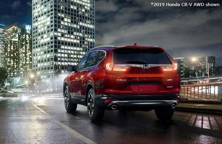 2019 Honda CR-V AWD driving on a wet road to a city at night