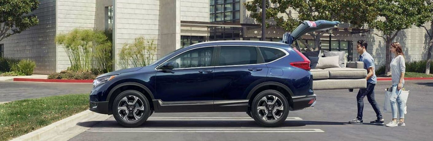 2019 Honda CR-V with a couple loading a couch into the cargo area