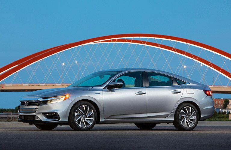 2020 Honda Insight exterior side shot with gray silver paint color parked in front of a red arch bridge in the early night