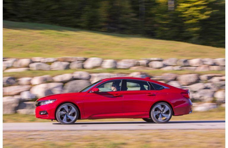 2020 Honda Accord Sport exterior side shot with red paint color driving alongside a rock and stone wall near fields of grass