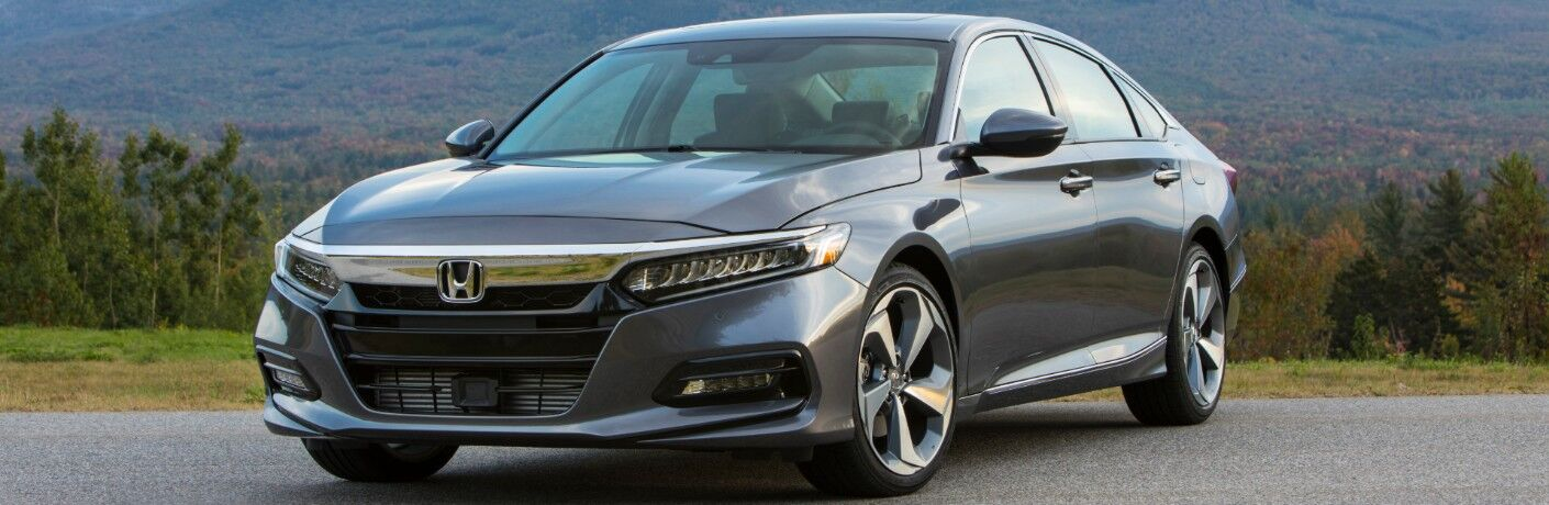 2020 Honda Accord Touring exterior shot with gray metallic paint color parked on an asphalt walking path with a background of forest trees and mountain hills