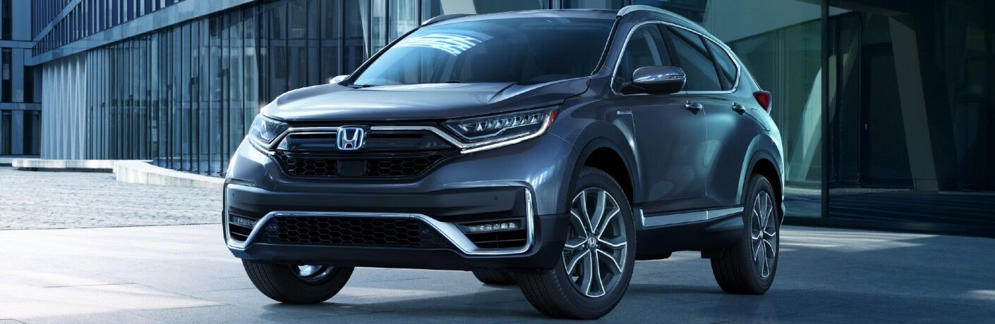 2020 Honda CR-V Hybrid exterior shot with parked on concrete outside a metal and glass building