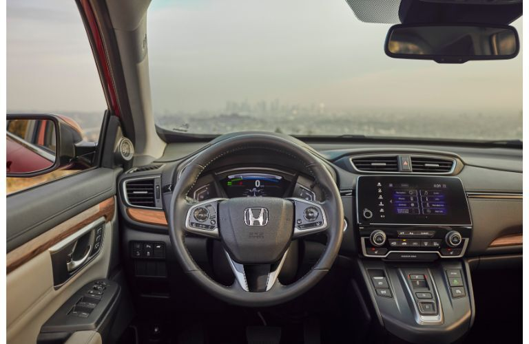 2020 Honda CR-V Hybrid interior shot of driver's seat view of steering wheel, transmission, infotainment screen, and dashboard