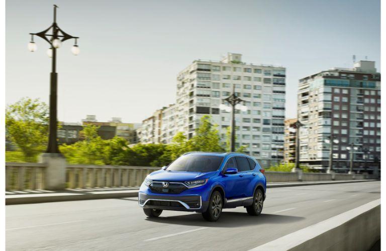 2020 Honda CR-V Touring exterior shot with blue paint color driving across a city concrete bridge