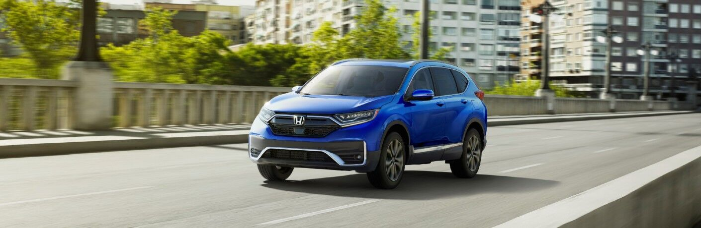 2020 Honda CR-V Touring exterior shot with blue paint color driving over a concrete city bridge