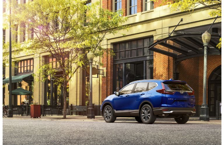 2020 Honda CR-V Touring exterior side shot with blue paint color parked outside a city cafe