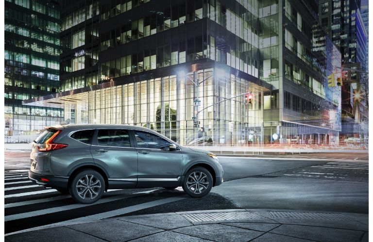 2020 Honda CR-V Touring exterior side shot with gray metallic paint color at an intersection in a lit up nighttime city