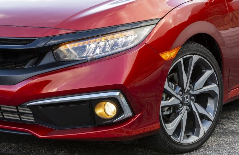 2020 Honda Civic Sedan Touring exterior closeup shot of front headlights, wheel, tire, and bumper with Molten Lava Pearl paint color