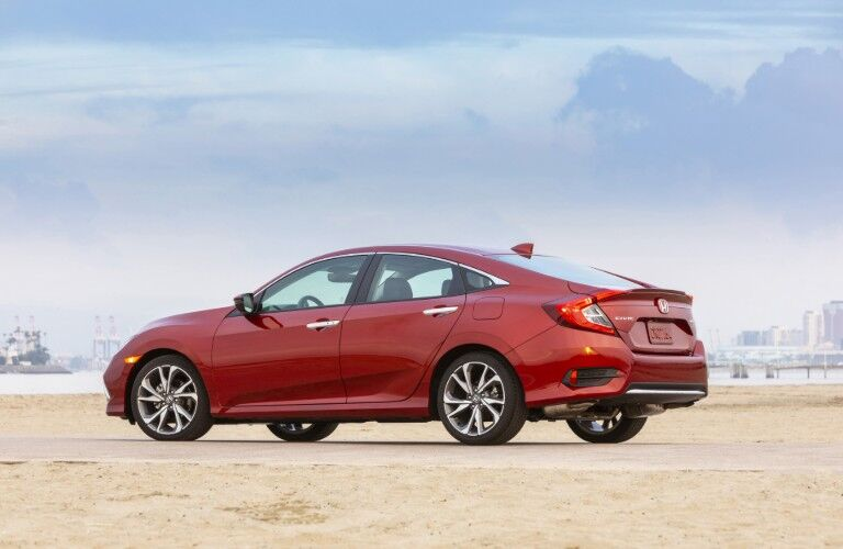 2020 Honda Civic Sedan Touring exterior side shot with Molten Lava Pearl paint color parked on a bright sandy beach