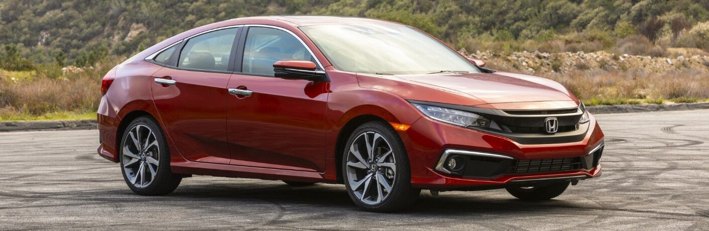 2020 Honda Civic Touring Sedan exterior shot with Molten Lava Pearl paint color parked on an asphalt lot near dry grass, shrubs, and trees