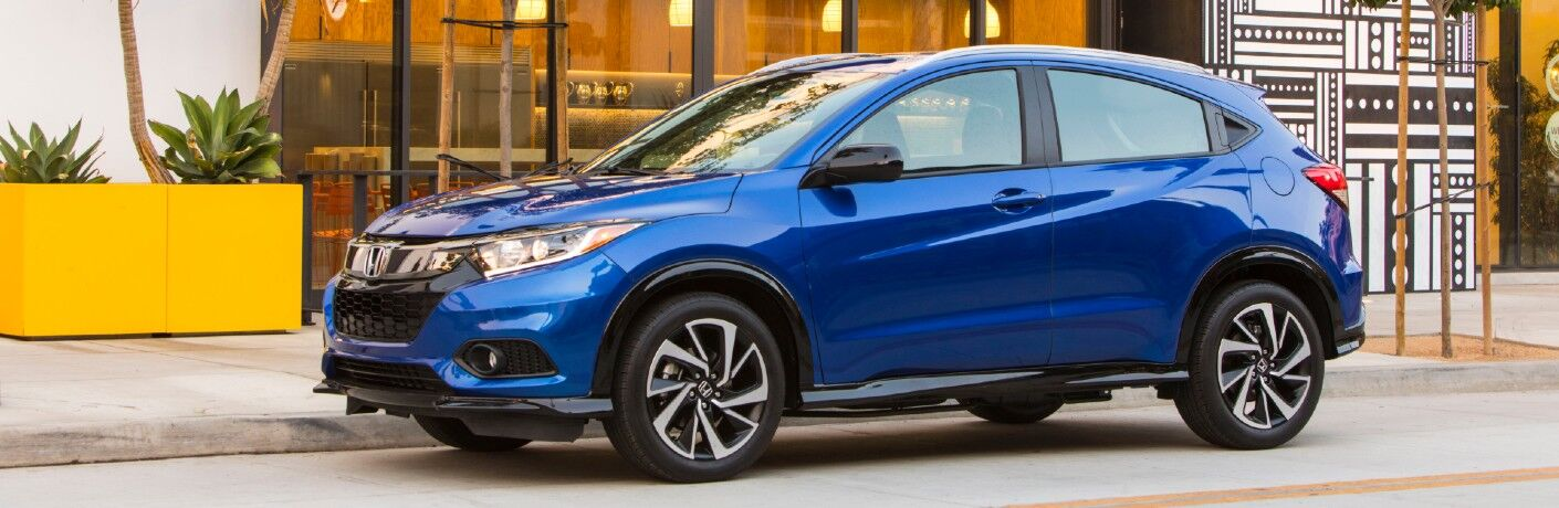 2020 Honda HR-V Sport exterior side shot with blue paint color parked outside a cafe restaurant