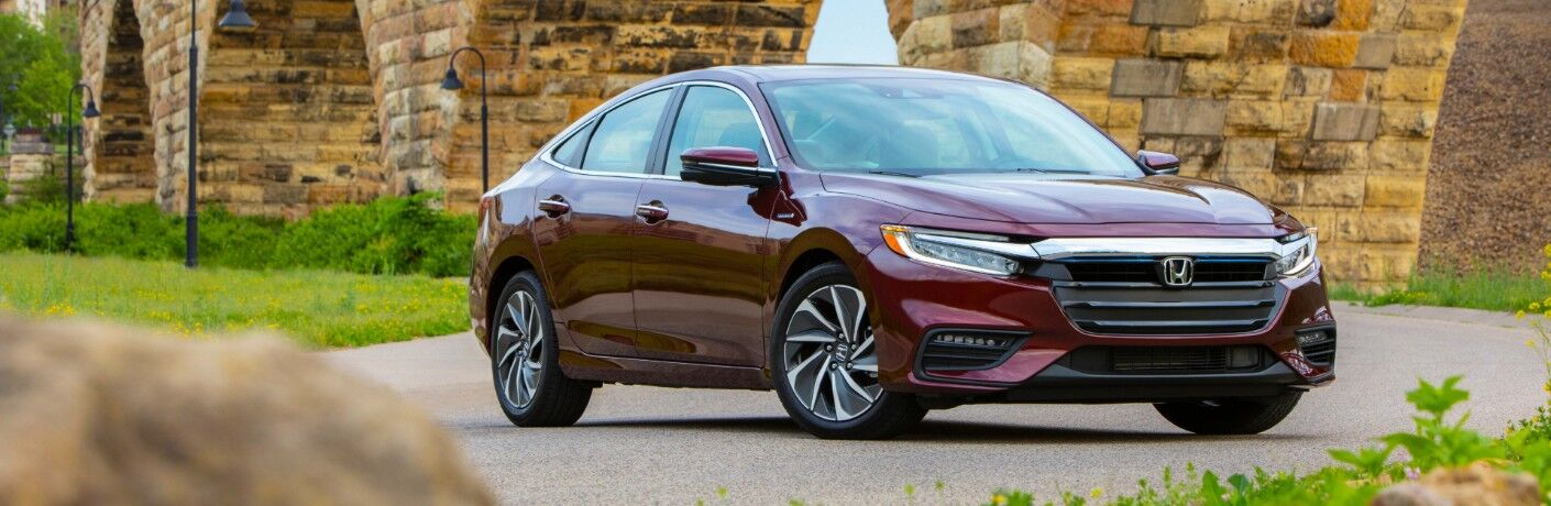 2020 Honda Insight exterior shot with crimson pearl paint color parked near brick arches of a bridge